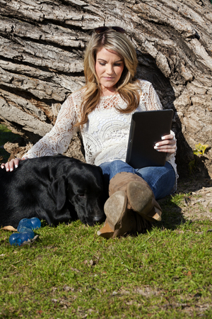 human being: Young woman using a computer tablet sitting and embracing her dog black labrador in Trinity Park in downtown Ft Worth, Texas.  Composition showing that dog and human being are two best friends.  Copy Space