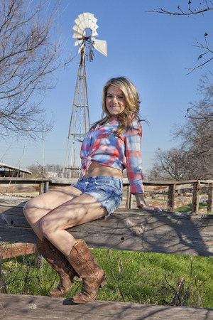 Cowgirl sitting on fence with windmill in background Banco de Imagens