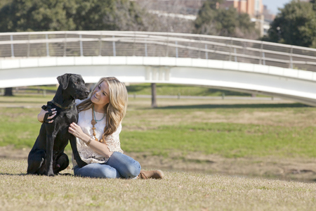 human being: Young woman sitting and embracing her dog black labrador in Trinity Park in Ft Worth, Texas.  Composition showing that dog and human being are two best friends.  Copy Space