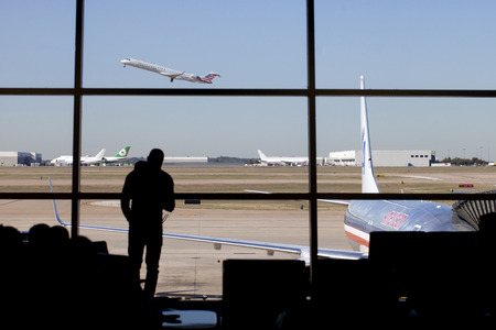 air travel: Silhouette of man standing infront of window watching an airplane take off at Dallas - Fort Worth (DFW) airport in Texas,