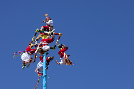 brilliantly: The voladores, or flyers, of Tulum dress in brilliantly colored traditional costumes, climb up a very high pole (about 100 feet) tie their waist to ropes wound around the pole and then jump off, flying gracefully around and around the pole as the ropes  Editorial