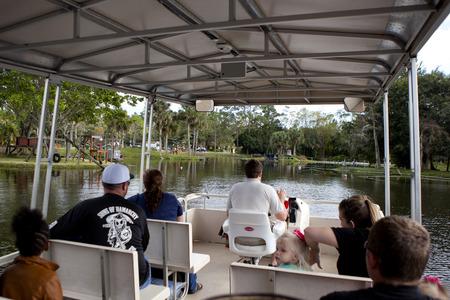 educacion ambiental: Turismo de montar en un pont�n barcos en el lago en el Lion Country Safari en Loxahatchee (cerca de West Palm Beach), Florida y aprender sobre la vida silvestre de estar en las islas en el parque Editorial