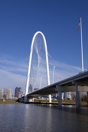 dallas: The new Margaret Hunt Hill Bridge that crosses the Trinity River with downtown Dallas, Texas in the background. The bridge uses a unique design of a 400-foot steel arch and cables to suport the bridge.