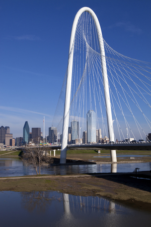 architectural feature: The new Margaret Hunt Hill Bridge that crosses the Trinity River with downtown Dallas, Texas in the background. The bridge uses a unique design of a 400-foot steel arch and cables to suport the bridge.