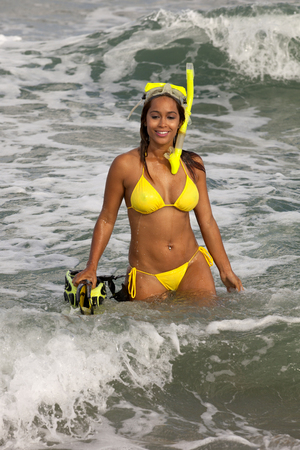 Pretty woman in sexy yellow bikini excited to be going snorkeling in the ocean