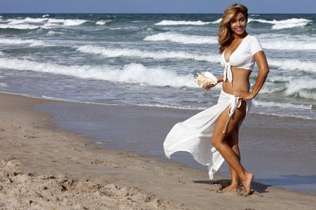 Beautiful woman walking on beach in a sexy white outfit carrying a seashell