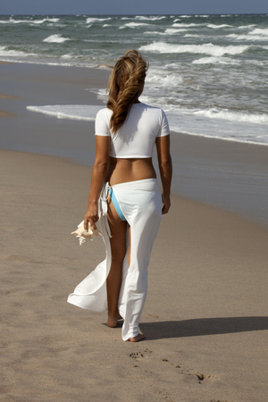 adult footprint: Beautiful woman walking on beach in a sexy white outfit carrying a seashell