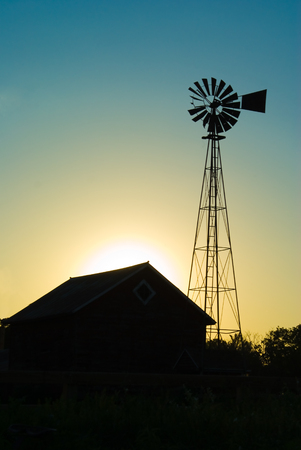 old farm windmill and barn at sunset