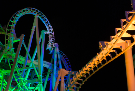 Modern rollercoaster lit up with different colors of light at night. Banque d'images
