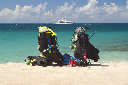Scuba tanks on a beach with boat in background