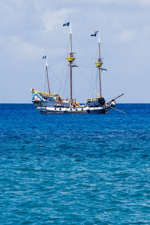 waters: Pirate sailboat anchored off shore in calm waters