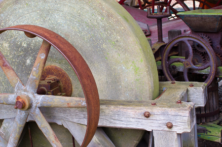 farm equipment: Old rusty abandoned farm equipment - Grinding stone Stock Photo