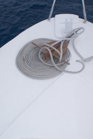 Rope coiled on the deck of a boat with anchor.