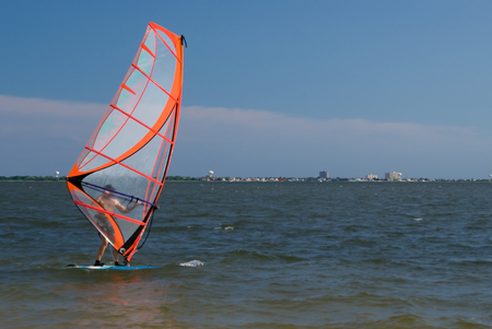 sailboard: Man (baby-boomer) going windsurfing in the ocean Stock Photo