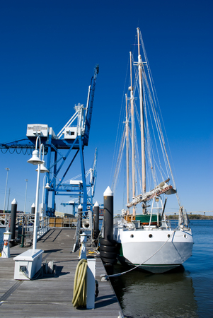 loading dock: Sailboat at dock not far from a large loading dock crane and wharf