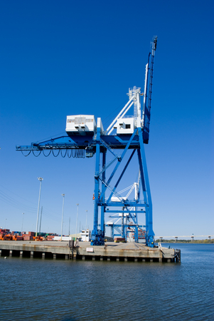 south space: Steel cargo crane with shipping containers stacked on a dock, in Charleston, South Carolina. Copy Space