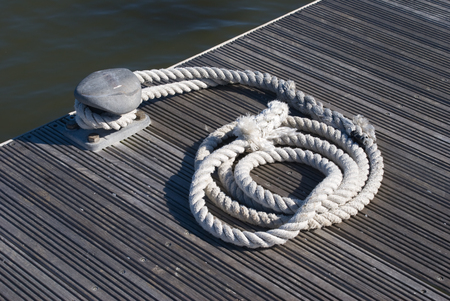 corded: Rope coiled on the dock next to the water.