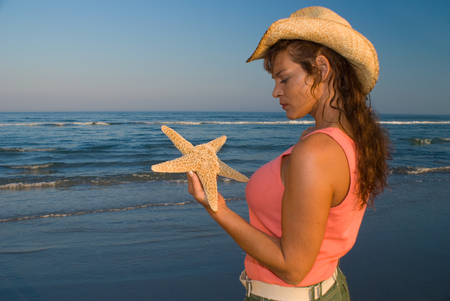 marinelife: Young adult woman holding a starfish and looking at ocean