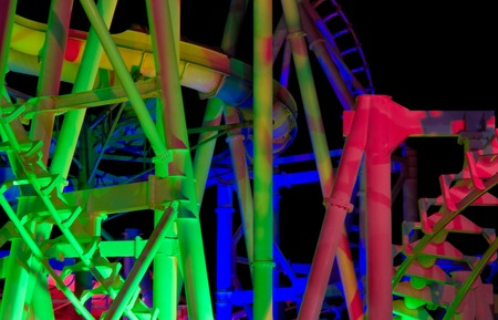 wildwood: Modern rollercoaster lit up with different colors of light at night. Stock Photo