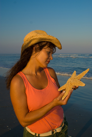 Young adult woman holding a starfish and looking at ocean