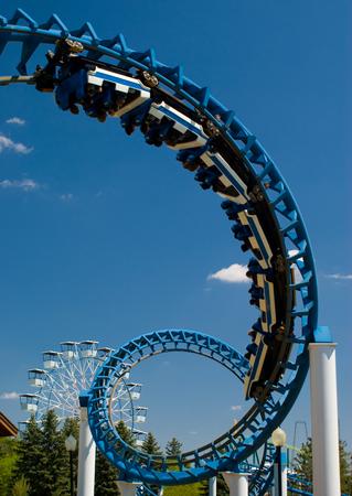 Cork-screw Rollercoaster and Ferris-Wheel at amusement park. Slight motion blur on Rollercoaster cars Editorial