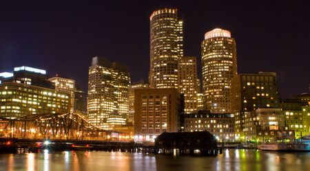 View ofthe skyline of Boston Massachusetts at night from across Fort Point Channel.