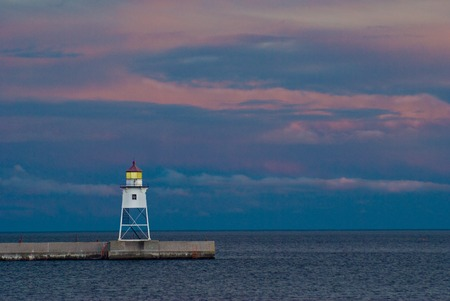 Grand Marais lighthouse at end of breakwater in Minnesota just after sunset Stock Photo