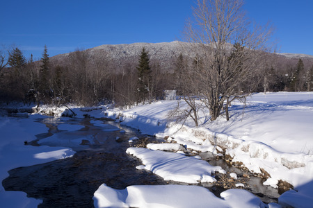 Scenic view of snow covered mountain stream at Mount Washington