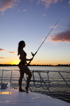 Silhouete of woman fishing on the bow of a boat