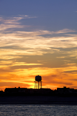 Silhouette of homes on a beach and watertower with clouds lit up in a dramatic colorful sunset. Avalon, New Jersey Banque d'images