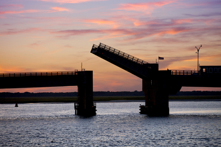 Silhouette of an open drawbridge between Avalon and Sea Isle City in New Jersey just after sunset.
