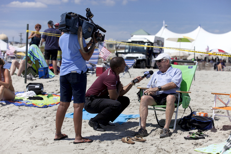 Tourist being interview by news crew on the beach at the Atlantic City Air Show in New Jersey.