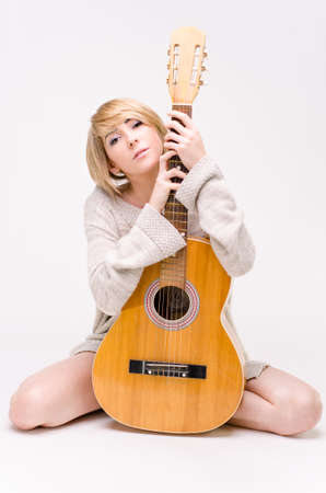 Young beautiful smiling blonde lady in gray sweater playing acoustic guitar photo