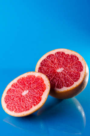 Whole and sliced on half grapefruit on a blue background, vertical shot
