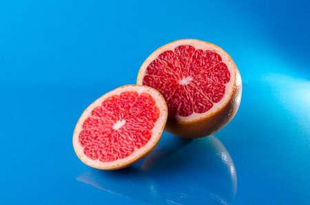Whole and sliced on half grapefruit on a blue background, horizontal shot