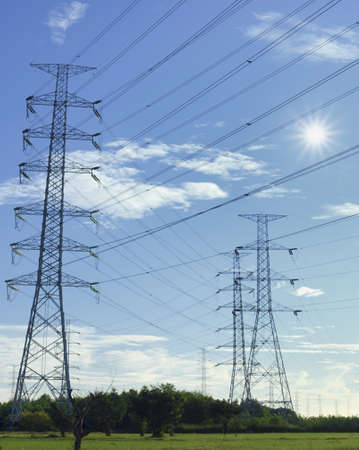 The tower of high voltage line with blue sky and sun. photo