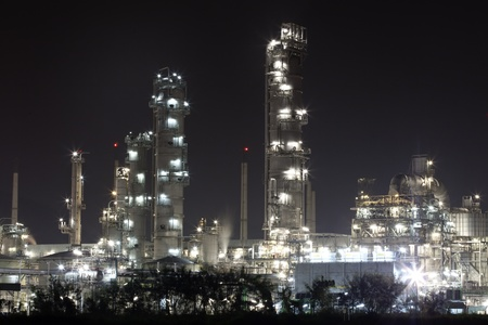 outdoor lighting: scenic of petrochemical oil refinery plant shines at night, closeup Stock Photo