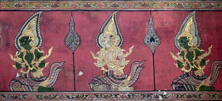Ancien angel and demon picture on the wall in Thai temple. This picture is over 200 year old in Wat Yai, Thailand. photo