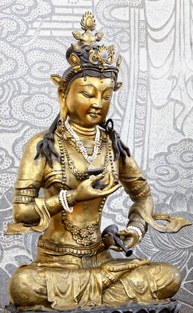 mercy: Statue of Golden Kuan Yin with stone picture background.