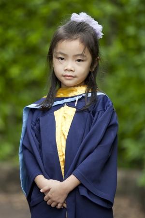 birrete de graduacion: El logro de grado para chica joven en la naturaleza verde. Foto de archivo