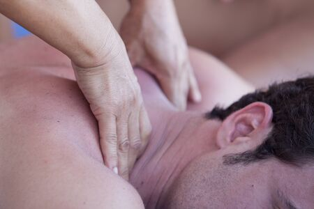 male massage: Close-up of an attractive man having a back massage in a spa center