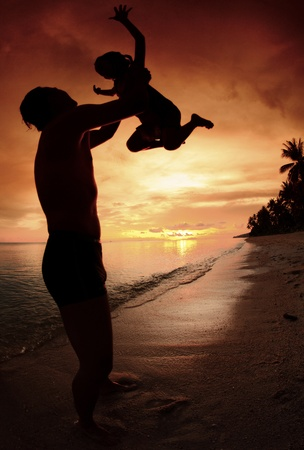 silhouette family of child hold on father hand with sea view. photo