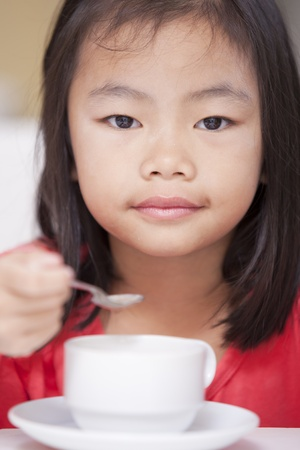Pretty girl eating rice gruel with the cup  Stock Photo - 13327359