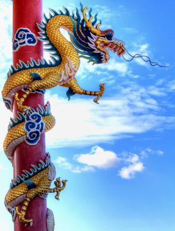 colum: Giant golden Chinese dragon with red colum and blue sky