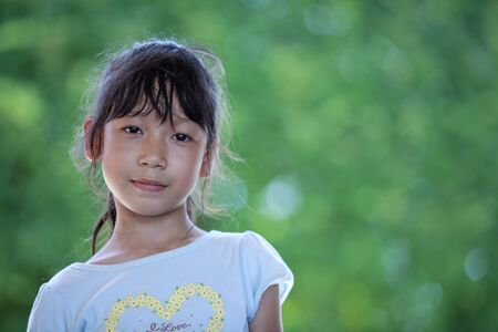 multiracial children: The asian girl with green nature background  Stock Photo