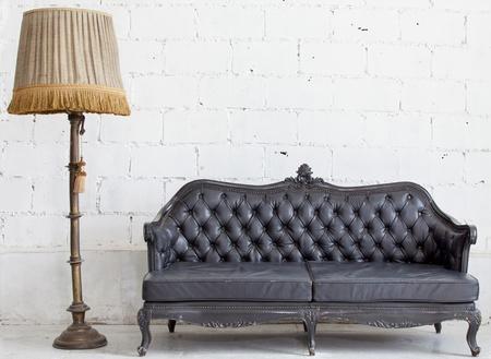 white sofa: leather black antigue sofa in white room.