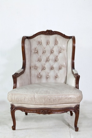 ancient white leather armchair whit white wall background. photo