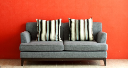 copy room: gray sofa put on red stucco background  Stock Photo