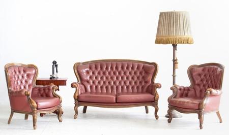 divano: divano in pelle antica con lampada e telefono in camera bianca