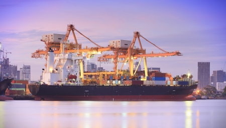 SHIPPING CONTAINERS: Container Cargo freight ship with working crane bridge in shipyard at dusk for Logistic Import Export background